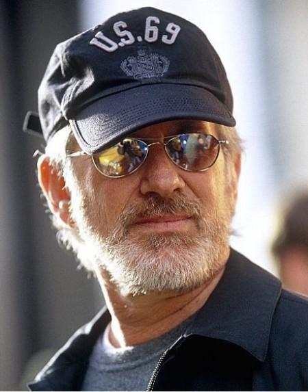 Spielberg shades his eyes because they're too bright for you.  Hence the hat, even without the glasses.